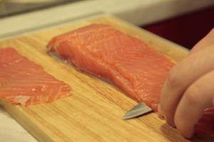 Нарежьте слабосоленую семгу тонкими широкими полосками.