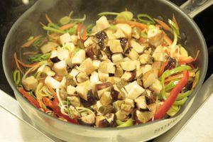 На тарелку выложить макароны, оформить обжаренными овощами, посыпать зеленью.