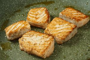 На другой сковороде обжарить кусочки рыбы до румяного цвета, примерно по 1,5 минуты с каждой стороны. Снять с огня в теплое место.