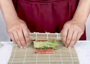 Возьмите большой лист салата, положите перед собой, выдавите с к одного края сыр полоской, сверху на него положите нарезанные овощи. Закрутите в виде рулета
