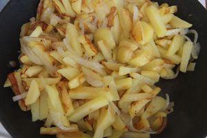 Добавьте тонко нарезанный репчатый лук, жарьте до готовности картофеля, еще минут 7-10, в зависимости от мощности плиты. Часто не мешайте, иначе картофель превратится в кашу. В конце посолите, поперчите по вкусу.