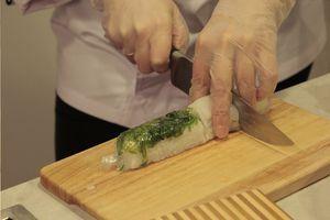 Прижать рукой края коврика к полученному роллу. На половинку ролла положить каракатицу, на вторую половину выложить салат Чука. Обернуть все пищевой пленкой.