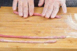 На посыпанную мукой доску выкладываем розовое тесто, делим на порции, катаем тонкие жгутики. Чем тоньше жгутики, тем красивее получится рисунок.