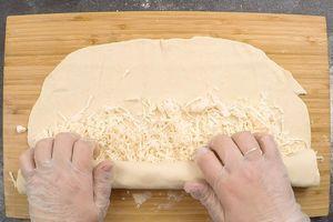 Сверху посыпать тертым сыром, скатать в рулет, защипнуть края.
