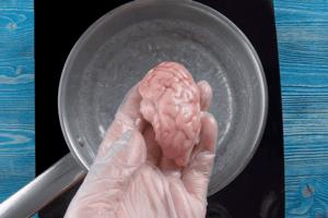 Мозги разморозить естественным способом, промыть под холодной водой. В кастрюле воду довести до кипения, проварить мозги 5-7 минут.