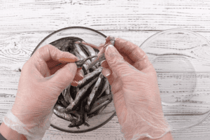Рыбу разморозить естественным способом на нижней полке холодильника, промыть под холодной водой (если есть поломанные рыбки — не страшно, для тушения они тоже подойдут). Удалить голову с кишечником (руками, как мы, или с помощью ножа: сделать надрез над головой со стороны спинки и потянуть — внутренности вытянутся вместе с головой).