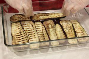 Подготовить форму для запекания с высокими бортами: первым слоем выложить половину баклажанов, затем половину фарша, затем снова баклажаны, фарш. Последний слой смазать густым соусом.