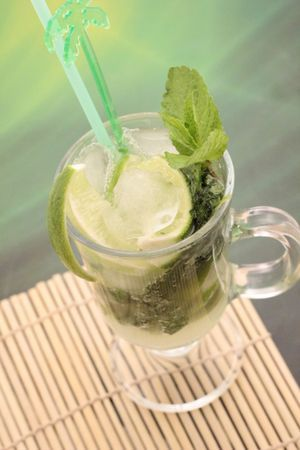 В бокал для коктейля положить лайм и мяту, хорошо размять. Влить сироп, добавить лед. Залить газированной водой.