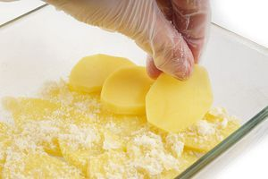 Сверху посыпать сыром и выкладывать так слоями, пока не закончится картофель. Накрыть фольгой, поставить в разогретую до 200С духовку примерно на 40 минут, до готовности картофеля.