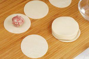 Достаньте готовое тесто из упаковки. В центр кружка выложите колобок из фарша.