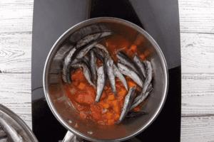 В кастрюлю с высокими бортами выложить часть овощной заправки, затем рыбу.