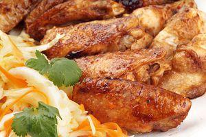 Выложите на тарелку готовые крылья и витаминный салат, украсьте зеленью.