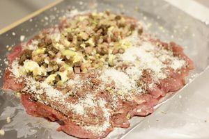 На рабочей поверхности расстелить фольгу, смазать оливковым маслом, в центр выложить мясо индейки в виде прямоугольника. Посыпать тертым чесноком и сыром.