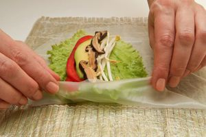 Выложить в центр листа начинку и накрыть ее краями рисовой бумаги.