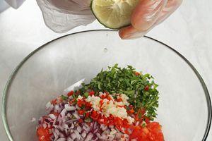 Приготовьте соус сальса: смешайте мелко нарезанные чеснок и перец чили, помидоры, сладкий перец, красный лук,  зелень кинзы. Заправьте соком лайма, коричневым сахаром, посолите, поперчите по вкусу.  Добавьте размолотые семена зиры. Перемешайте и дайте настояться 8-10 минут.