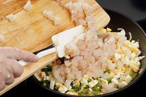 К луку добавить нарезанные вареные яйца и рыбу, посолить, поперчить по вкусу, перемешать.