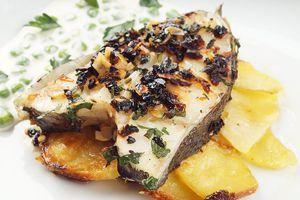 На тарелку выложить мильфей из картофеля, сверху стейк палтуса. Украсить зеленью и соусом.