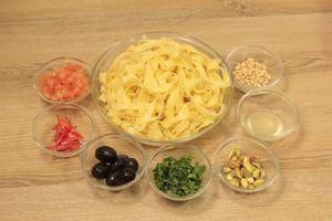 Отварить пасту в течение 8 минут в большом количестве воды (1:10). Сбрызнуть оливковым маслом, остудить. Перец чили нарезать тонкой соломкой, чеснок мелко порубить. С моркови и цукини, с помощью овощерезки, нарезать тонкие пластинки.