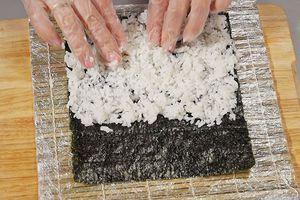 Водоросли нори положите вертикально, шершавой стороной вверх. Распределите равномерно рис, оставив сверху полоску ~2см.