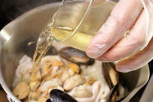Влейте в морепродукты белое вино и дайте немного ему выпариться