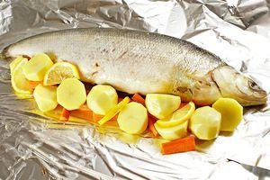 Вокруг зафаршированной тушки рыбы уложить овощи, дольки лимона, слегка посолить, поперчить