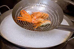 Отрежьте лобстеру голову. Все части лобстера слегка обжарьте в растительном масле, а затем окуните в кипящую воду на 5-10 секунд