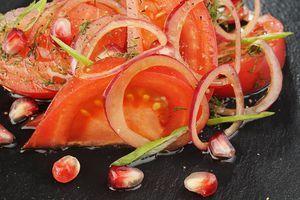 Помидоры нарезать крупными дольками, посолить, поперчить  по вкусу. Затем перемешать с луковой смесью. Выложить на тарелку, посыпать зернами граната и полить оливковым маслом. Украсить зеленым луком и перцем чили.