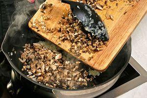 На разогретой с оливковым маслом сковороде обжарить лук до прозрачности, потом добавить  нарезанные грибы