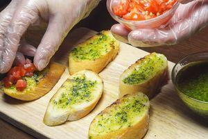 Обжаренный багет смазать соусом песто, сверху выложить нарезанный помидор (конкасе)