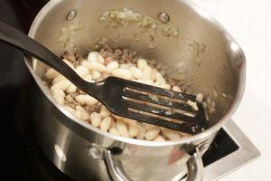 В разогретой кастрюльке на оливковом масле обжарить лук и чеснок, примерно 4 минуты, затем добавить фарш. Уменьшить огонь и готовить 5-6 минут, размешивая и убирая комки.