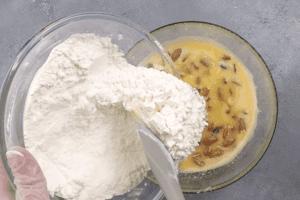 В яичную смесь добавить клюкву и орехи, затем всыпать муку и замесить пластичное тесто.