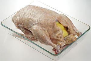 Подготовленную тушку муларда переложить в лоток для запекания, нафаршировать яблоками и чесноком. Можно добавить пару стручков перца чили.