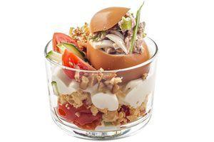 Яйцо наполните начинкой и установите на горку с овощным салатом. Украсьте зеленым луком, дольками помидора черри,  и рубленым грецким орехом.