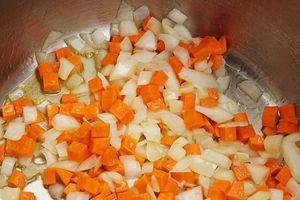 В глубокой кастрюле разогрейте растительное масло, обжарьте лук и морковь до золотистого цвета.