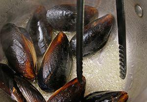 В кастрюльке разогрейте оливковое масло, обжарьте мидии 1-2 минуты