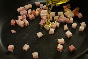 Бекон обжарить на разогретой сковороде, чтобы слегка вытопился жир, затем добавить оливковое масло