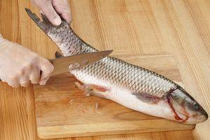 Рыбу разморозить естественным способом на нижней полке холодильника. Промыть под холодной водой от слизи. Обсушить бумажным полотенцем. Очистить от чешуи.