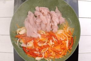 На разогретой с растительным маслом сковороде обжарить овощи, затем добавить куриное филе, жарить до полуготовности мяса.