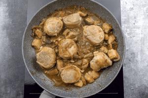Добавить к грибам соус, выложить сверху медальоны без шпажек и довести мясо до готовности.