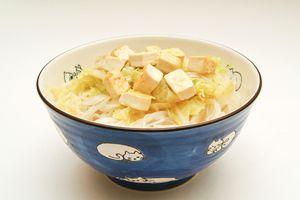 Добавить к рисовой лапше отваренную пекинскую капусту вместе с овощным бульоном, а сверху выложить обжаренный тофу.