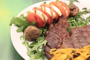 На тарелку с одной стороны выложить салат рукколу, помидоры и сыр моцареллу, нарезанные кружочками толщиной 1-1,5см. Сбрызнуть оливковым маслом и соевым топингом. Рядом положить грибы - гриль. С другой стороны выложить обжаренный стейк, украсить нарезанным перцем -гриль.