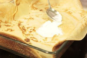 """(Отдельно отложить 2 блина.)   Форму для выпекания смазать маслом. В центр на дно выложить 1 блин, смазать сметаной, затем слегка внахлест выкладываем еще 5-6 блинов в форме """"цветка""""."""