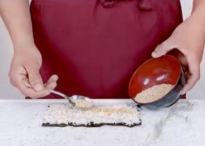 На лист нори выложите рис, оставляя небольшой нахлест.