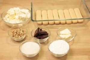 Желатин замочить в холодной воде на 10 минут. Шоколад поломать на кусочки, смешать с сливочным маслом. Сыр смешать с сахарной пудрой. 2/3 орехов  мелко порубить ножом.