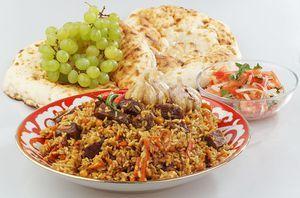 Перемешиваем готовый плов. Выкладываем на большую тарелку. К плову подаем салат из свежих овощей: помидоры дольками и лук. Свежую лепешку и виноград.