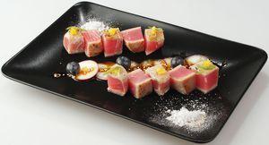 Нарежьте готового тунца на равные кубики 2*2см, выложите на тарелку. Украсьте овощами и ягодой, полейте дрессингом.
