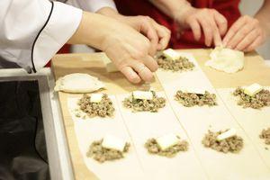 Раскатанное тесто нарезать на прямоугольники, с краю выложить начинку и по 1 кусочку сливочного масла на фарш. Закрыть второй половинкой теста и хорошо защипать края.