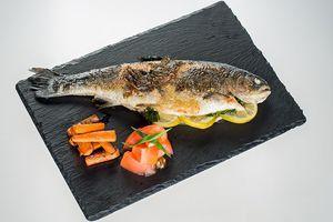 Готовую рыбу выложить на тарелку, украсить брусочками моркови, свежими овощами и зеленью.
