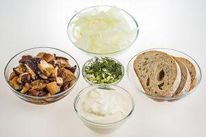 Белые грибы разморозить естественным способом на нижней полке холодильника, хорошо промыть, слегка обсушить. Нарезать крупным кубиком. Лук репчатый нарезать полукольцом. Зелень мелко порубить.