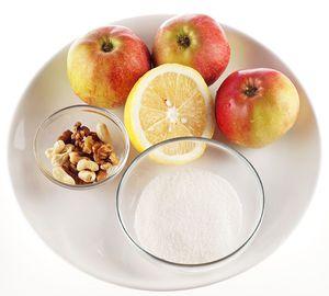 Яблоки промойте, нарежьте крупными дольками, сбрызните лимонным соком, разбавленным водой, чтобы не потемнели. Орехи мелко порубите.
